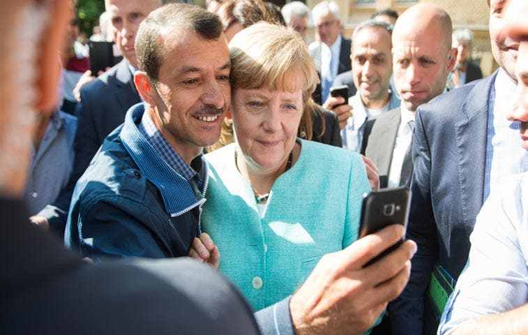 Refugiados reciben a Merkel con aplausos en oficina de migración