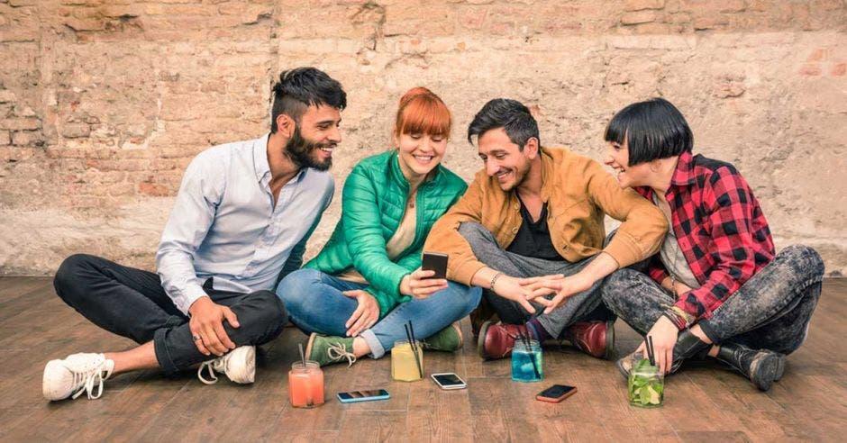 Un grupo de cuatro jóvenes comparten ideas en un cuarto.