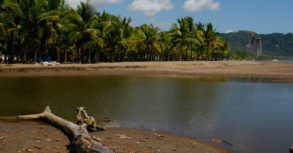 Imagen de una playa en Jacó en un día soleado. Edificios a medio construir se ve en el horizonte.