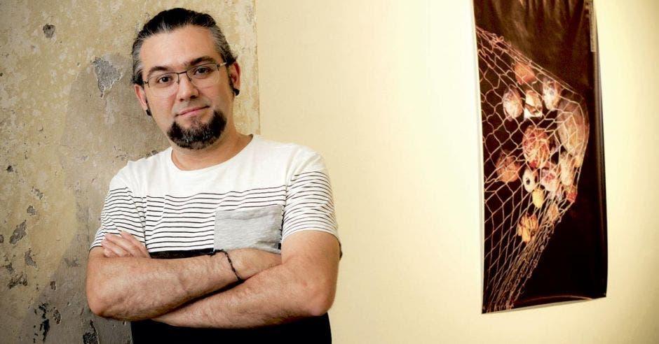 Diseñador José Vargas al lado de su afiche