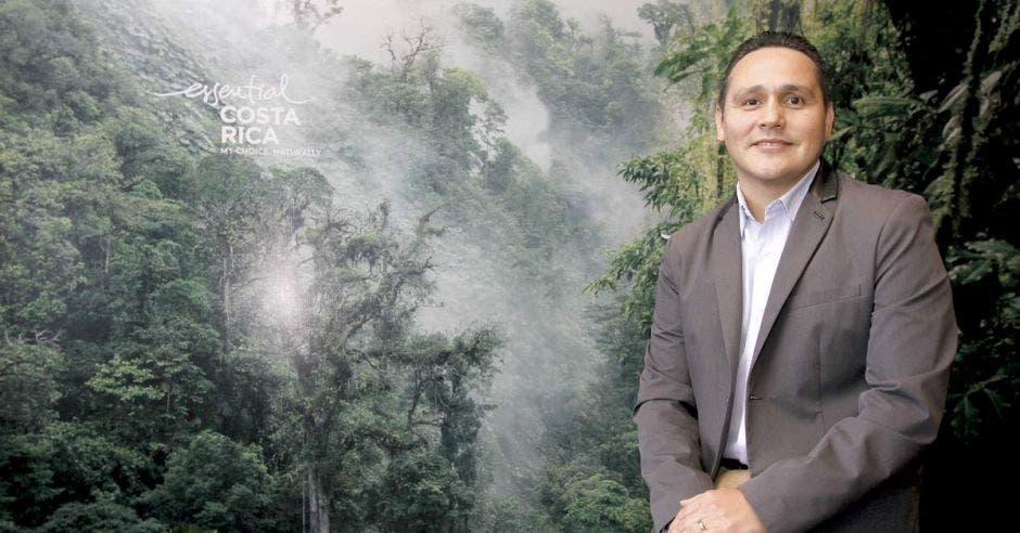 Alberto López, gerente general del ICT, posa sobre un póster de árboles y neblina.