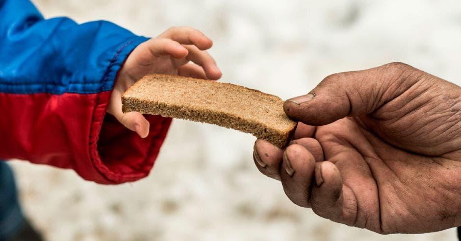 Niño hambriento toma rebanada de ban de una mano bondadosa
