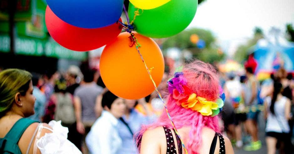 Joven de cabello rosa está de espalda sosteniendo unos globos de colores en la marcha
