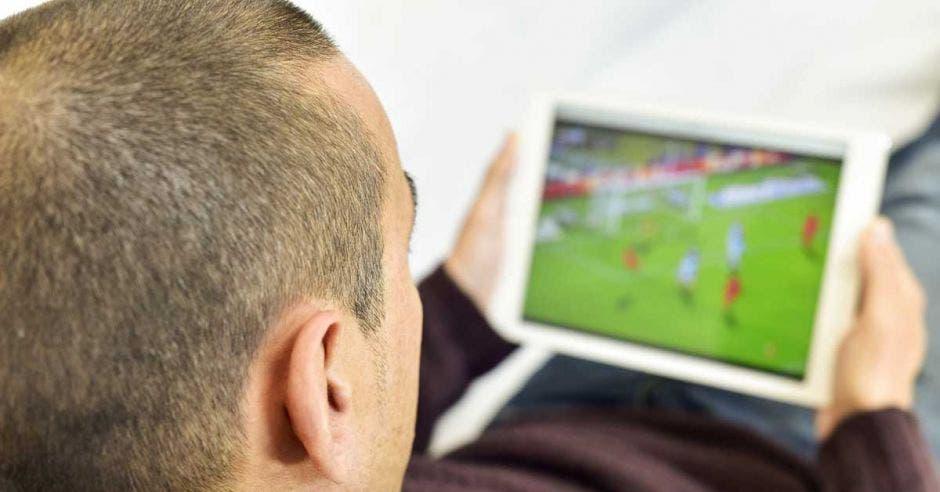 Un hombre mira un partido en streaming con su tablet.