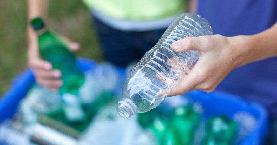 Una mano de hombre sostiene una botella de plástico