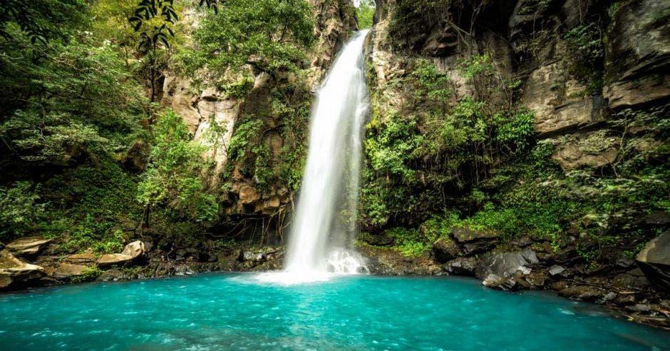 Una cascada cae sobre un río color celeste