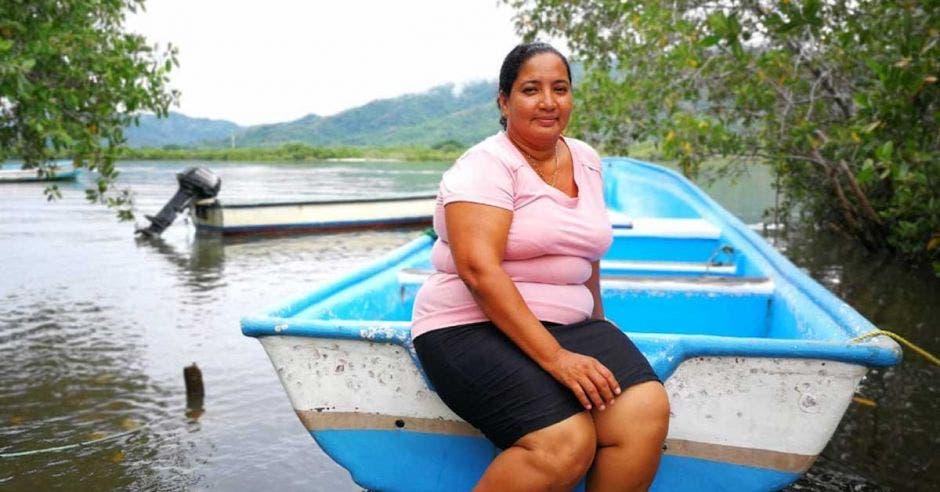 Sonia Medina, pescadora, posa en su bote cerca de un lago.