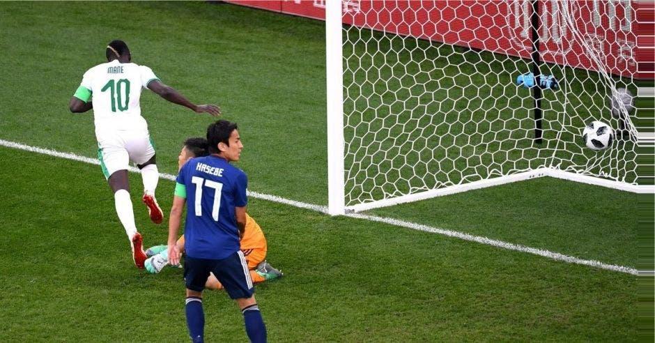 Sadio Mane celebra el primer gol de Senegal, ante la mirada de dos jugadores japoneses