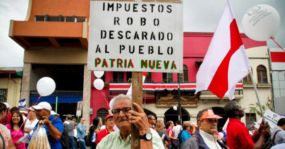 Un hombre sostiene una pancarta con una leyenda en contra de nuevos impuestos