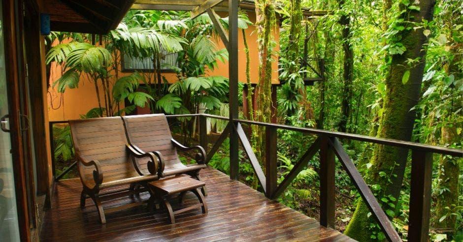 Una zona del hotel al aire libre con dos sillas de madera para admirar el paisaje