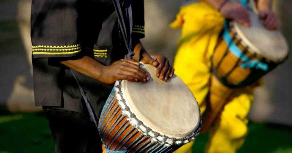 Dos afrodescendientes tocando  tambor tipo bongo