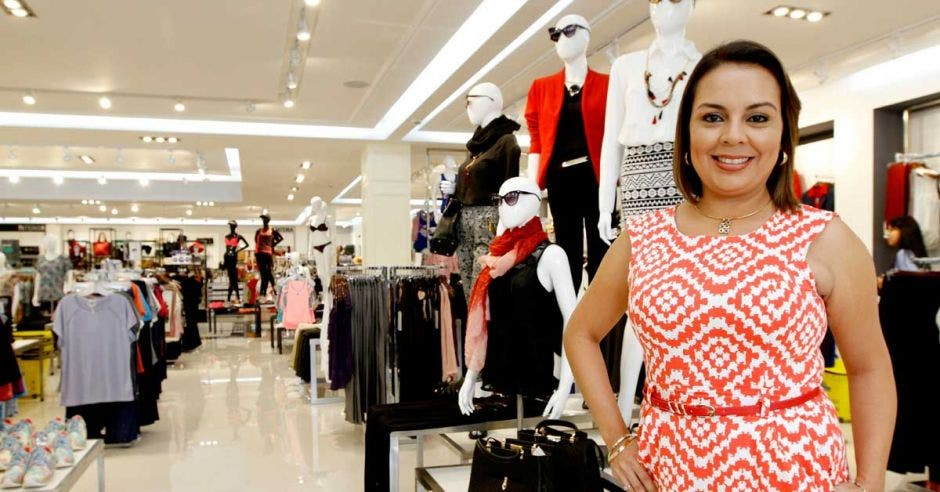 Natalia Reyes, de Ekono, posa con un vestido rojo frente a la ropa en la tienda Ekono de Guadalupe
