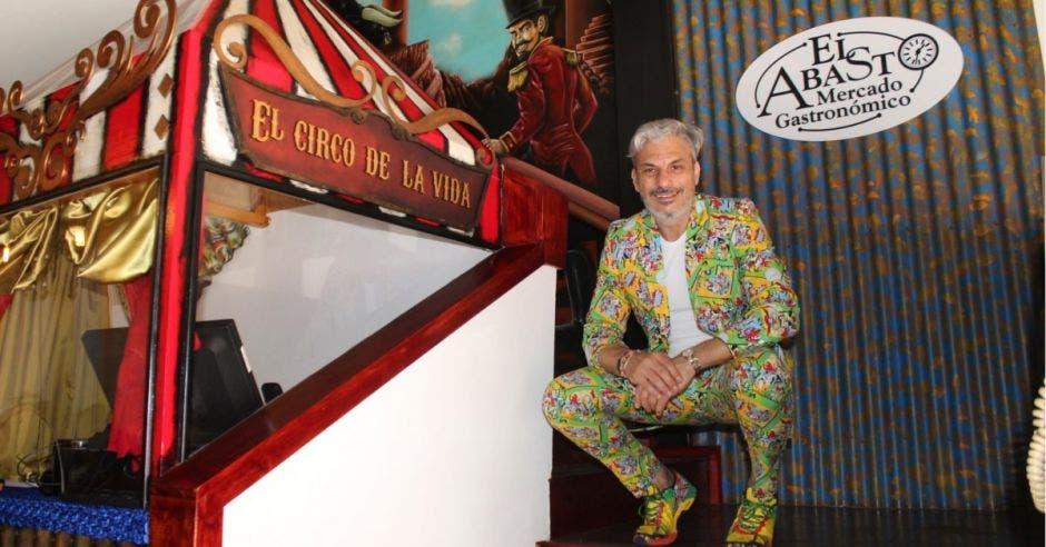 El propietario Jorge Saggal de cuclillas en las gradas del restaurante