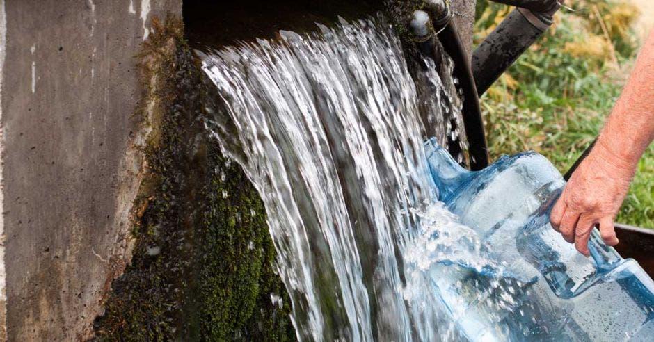 Una persona recoge agua con un bidón de plástico