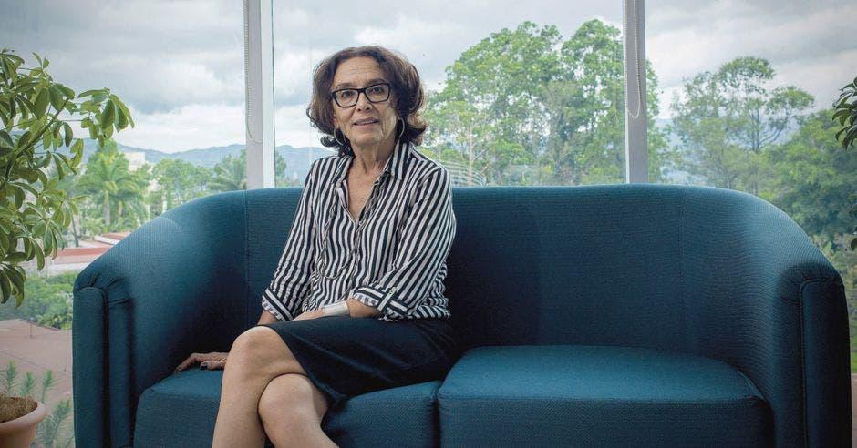 La ministra Patricia Mora sentada en un confortable sillón. Al fondo se ve un ventanal que deja al descubierto varios árboles