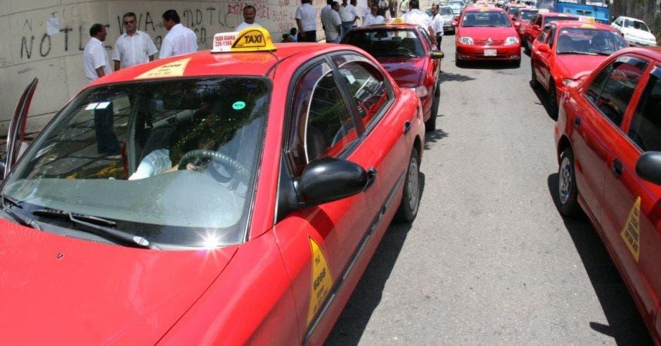Una fila de vehículos taxis haciendo presa