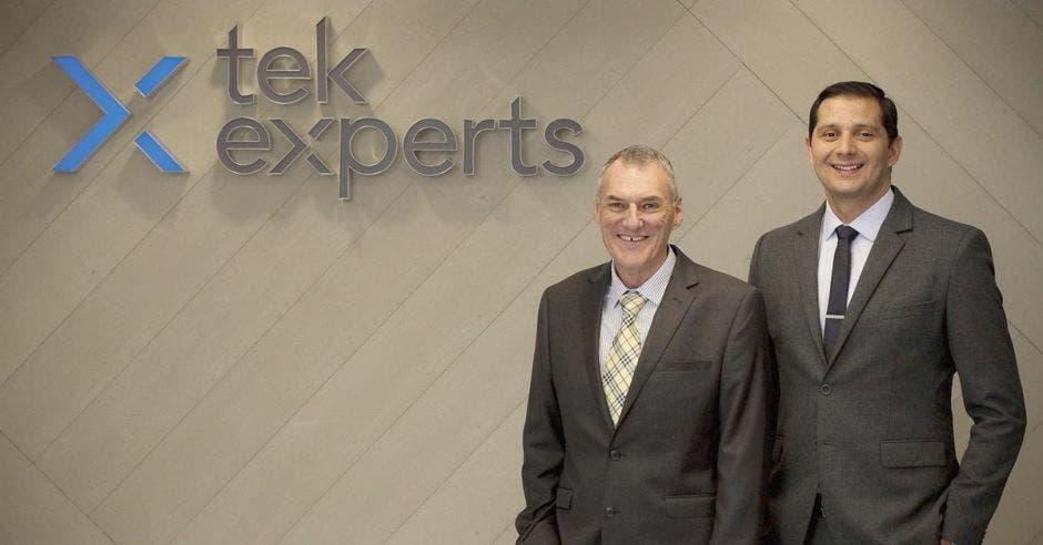Guillermo Campos y John Earley posando para la foto, de fondo el logo de la empresa