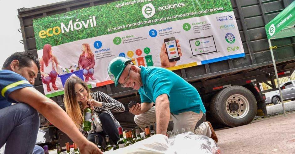 Un voluntario de ecolones recoge el material reciclado junto a dos clientes.