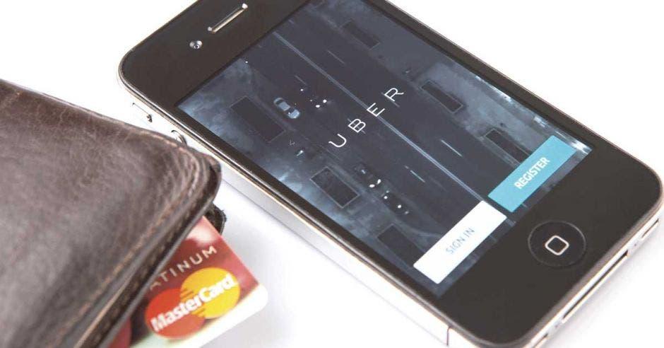Una billetera, un celular y una tarjeta sobre una mesa.