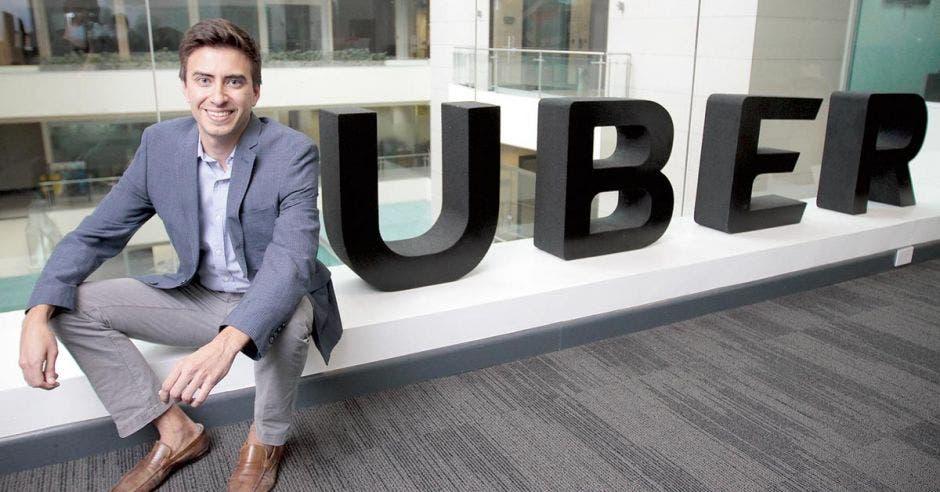 el gerente de uber sentado frente a un letrero de la empresa
