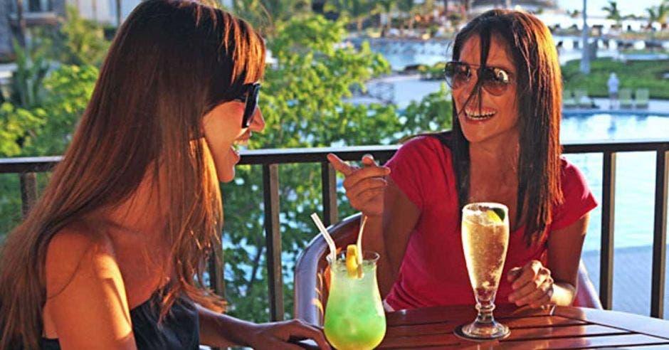 dos mujeres tomando refresco con pajilla