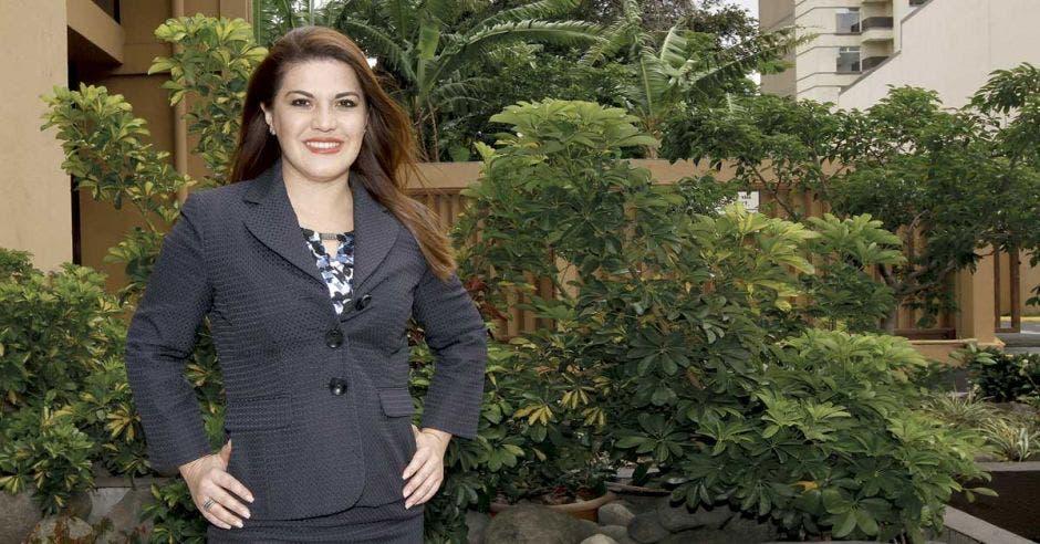 Ana Lucía Ramírez, directora ejecutiva de Infocom, posa en el jardín de la institución con un blaser color azul
