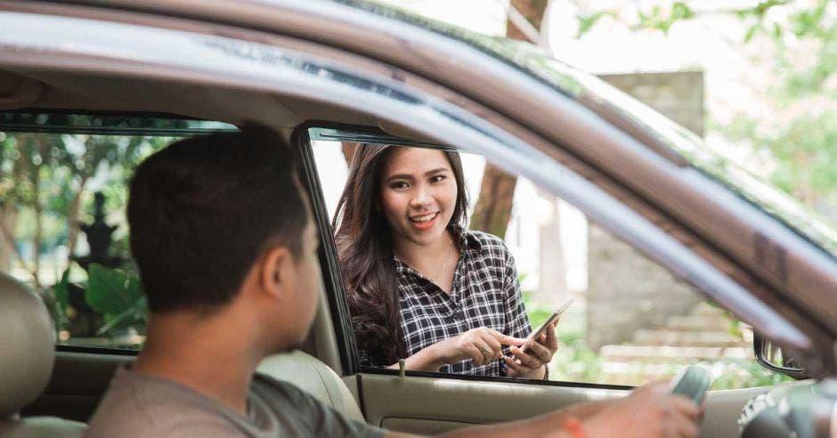 Una mujer pregunta a un conductor si es el Uber que pidió