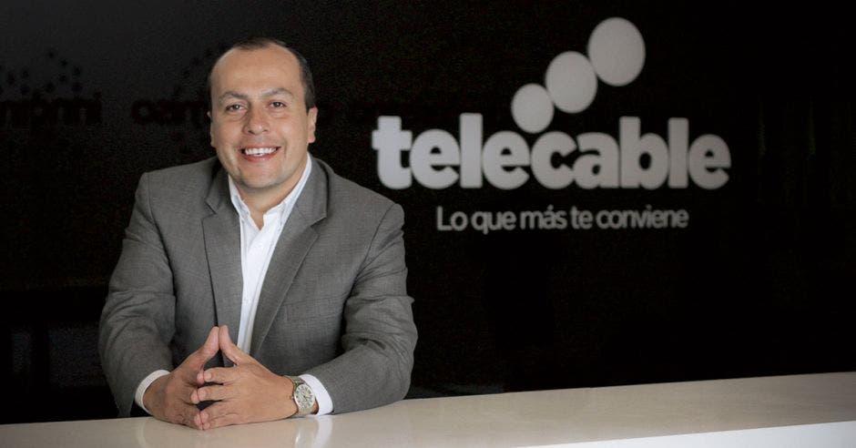 Rónald Jiménez, de Telecable, posa sonriente junto a un letrero de la empresa.