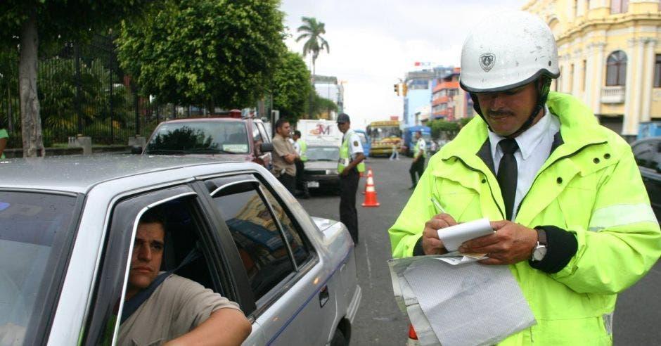 Un oficia revisa la información de un conductor