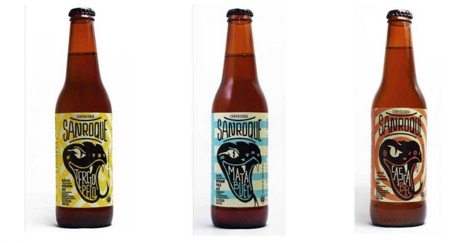 Tres botellas de cerveza con diferentes etiquetas, una amarilla, una celeste y otra anaranjada.