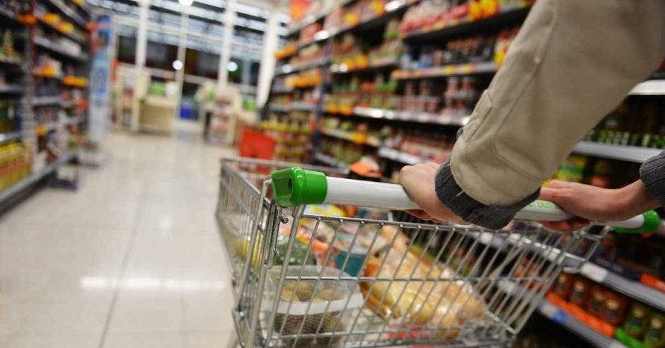 Un comprador lleva un carrito en un supermercado