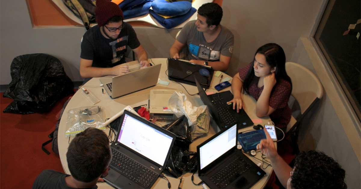 Un grupo de jóvenes trabaja en una mesa con computadoras