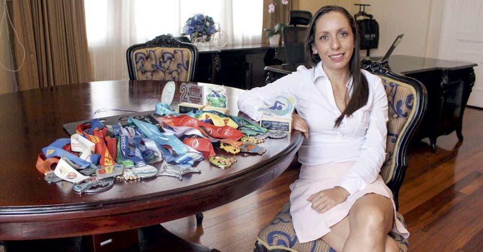 Carolina Hidalgo posa junto a sus medallas y trofeos que ha obtenido en aguas abiertas y eventos de mountain bike.