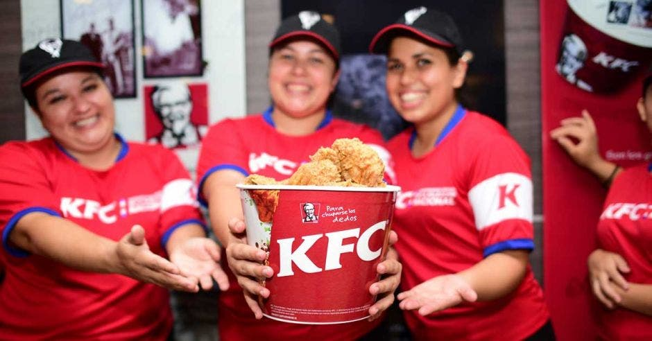 Tres empleadas de KFC sostienen una cubeta de pollo