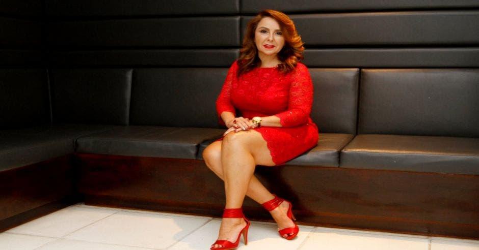 laura sentada en un sófa, con un vestido rojo