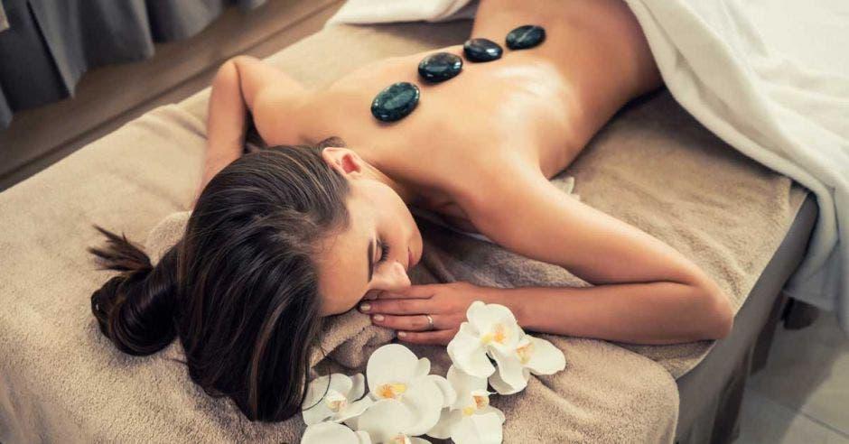 Mujer acostada en una cama de masajes