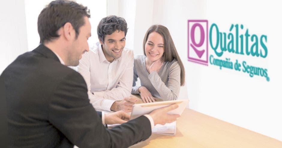 tres personas viendo algo en una tablet, atrás logo de Quálitas