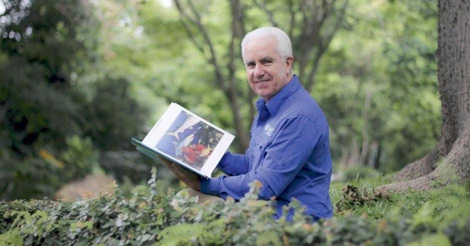 Carlos Uribe posa en un jardín con un libro de tiburones