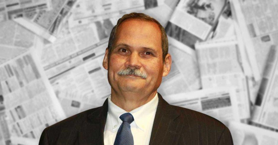 Luis Felipe Arauz sobre un fondo de periódicos
