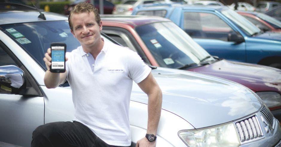 Carlos Martín posa con un celular cerca de la tapa de un auto