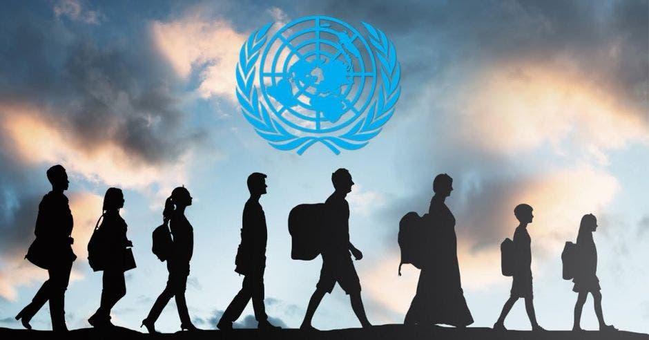 Varias personas caminan refugiadas y se ve el logo de la ONU