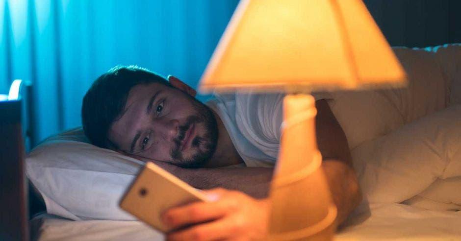 Un hombre mira su celular a la luz de una lámpara.