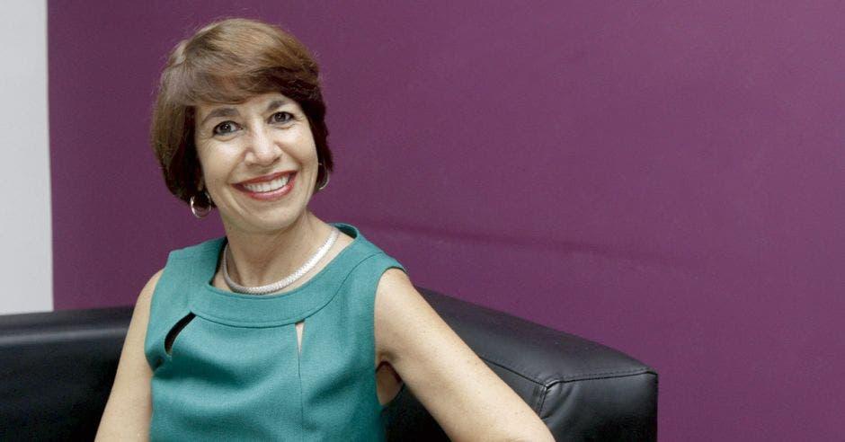 María Laura Arias posa en un sillón sobre una pared púpura
