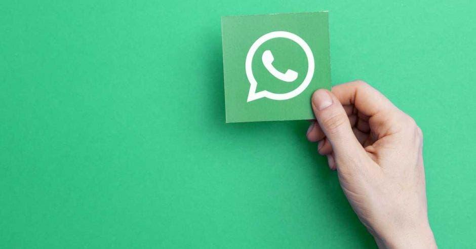 Una persona sostiene un papel con el logo de Whatsapp sobre un fondo verde