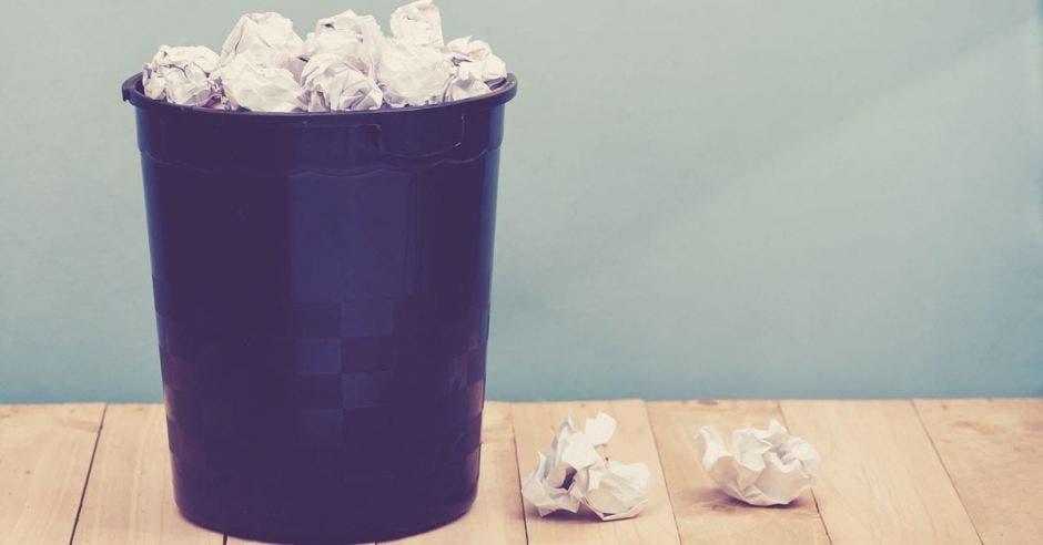 Un basurero con papeles a tope