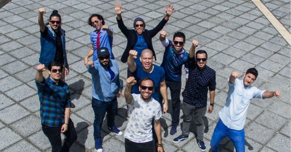 Los diez integrantes de la banda saludan hacia arriba