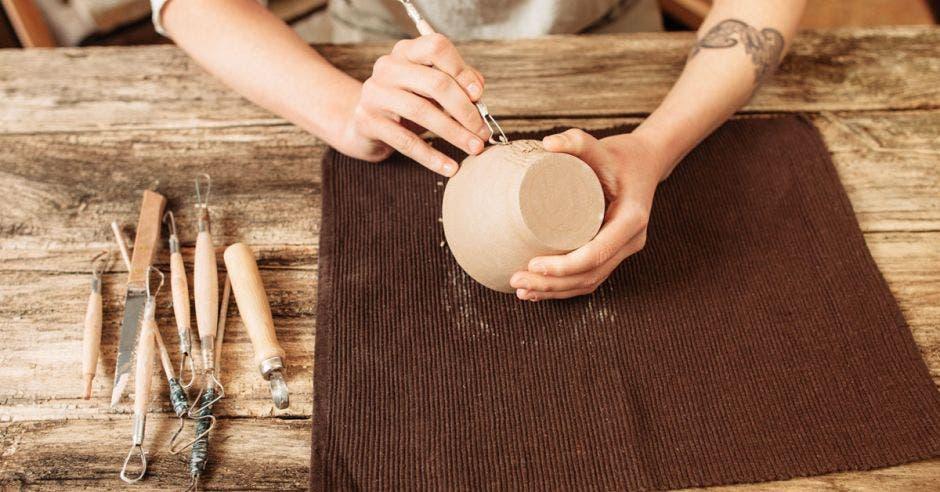 Una artesana detalla una vasija de barro