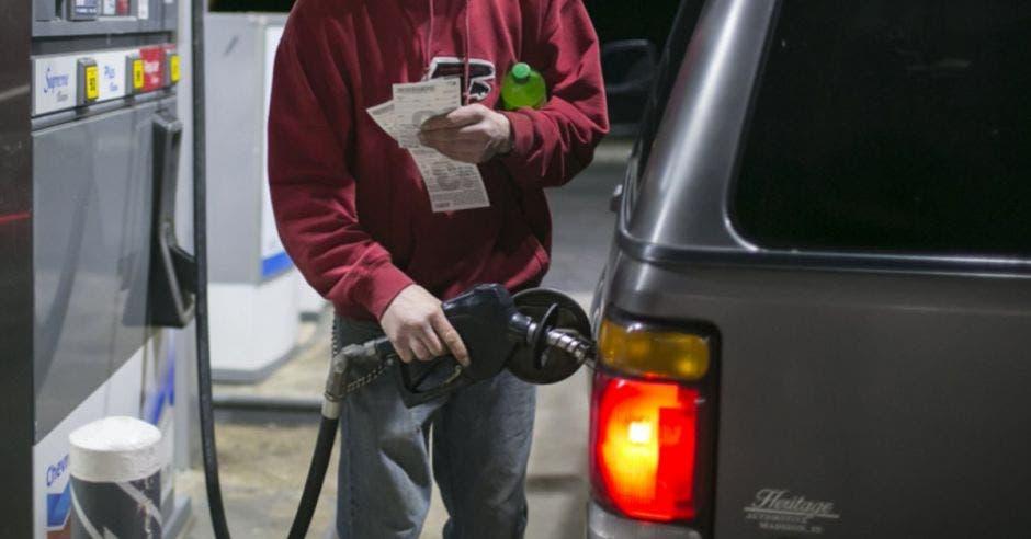 Un hombre llenando el tanque de combustible