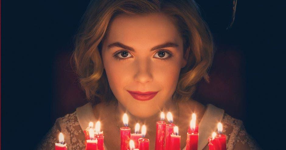 Sabrina la bruja frente a su queque de 16 años con velas rojas