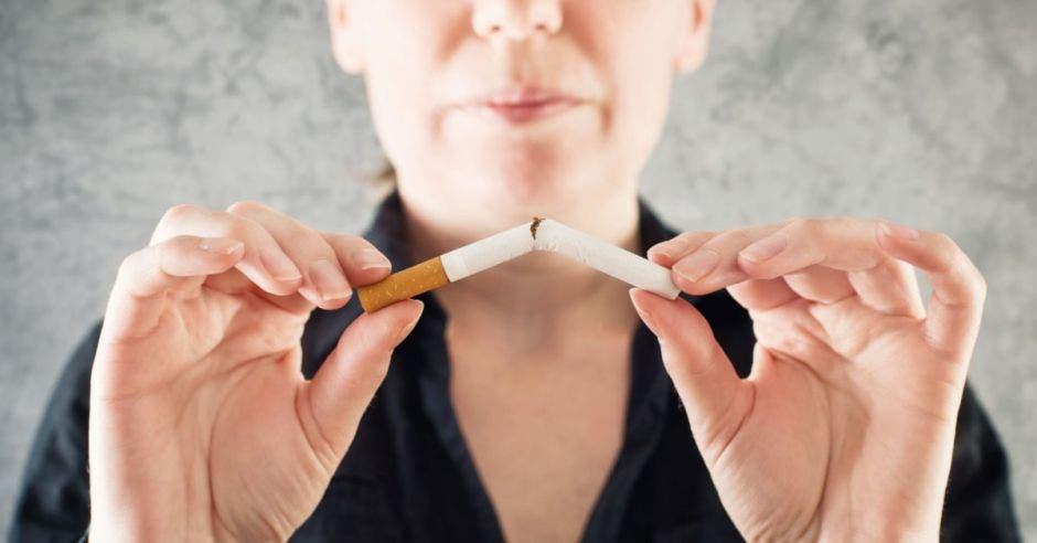 Una mujer rompe un cigarro en dos